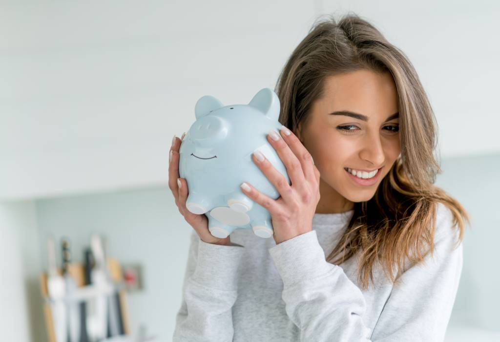 Happy young woman saving money in a piggybank - home finances concepts